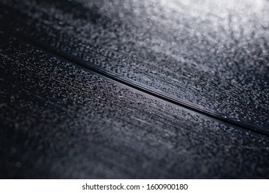 Abstract closeup of a vinyl record. The audio grooves are clearly visible. Vintage analog music.