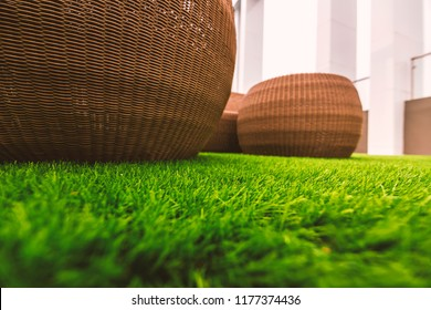 Abstract color between green artifical grasses and brown dasket weave.