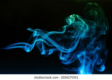 Abstract colored smoke moves on dark background. Wallpaper. Personal vaporizers fragrant steam. Concept of alternative non-nicotine smoking. E-cigarette. Texture. Design elements.