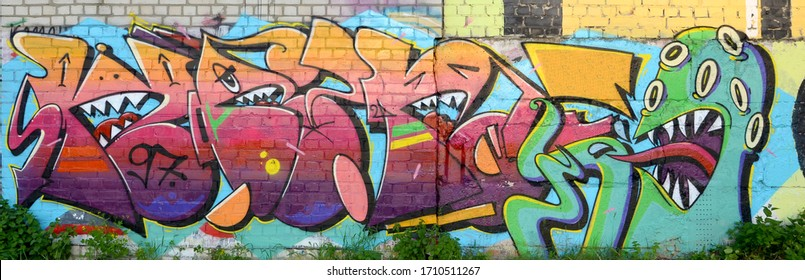 Abstract colorful fragment of graffiti paintings on old brick wall with scary octopus face. Street art composition with parts of unwritten letters and cartoon character