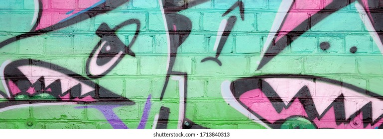 Abstract colorful fragment of graffiti paintings on old brick wall in green colors. Street art composition with parts of unwritten letters and multicolored stains. Subcultural background