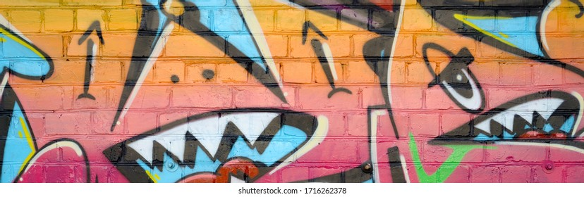 Abstract colorful fragment of graffiti paintings on old brick wall. Street art composition with parts of unwritten letters and multicolored stains. Subcultural background texture