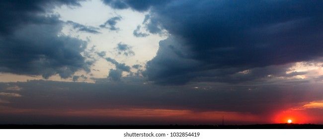Abstract colorful sunset background. Dramatic pink, yellow, orange and blue cloudy sky. Horizontal panoramic landscape with a face-shaped cloud