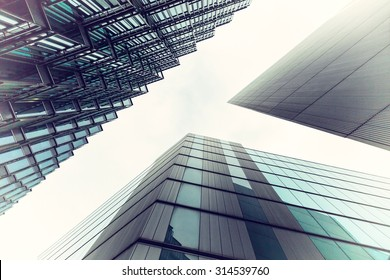 An abstract coloured vintage image, looking up capturing three different buildings on a 45 degree angle with an applied vintage filter to produce green and blue tint to the photo.