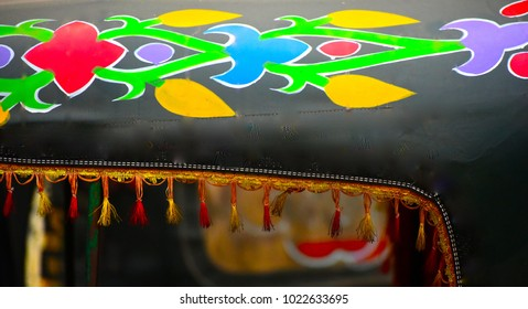 Abstract colourful design printed on a roof top of a tempo vehicle isolated objects photograph