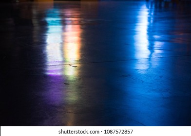 Abstract colourful reflection of lights on a polished dark floor.