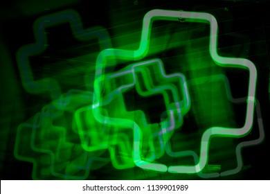 Abstract combined exposures of neon green cross marijuana dispensary symbol at night