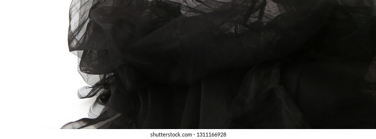Abstract composition of black tulle material  isolated on white background. Waving shape of tulle fabric with copy space.