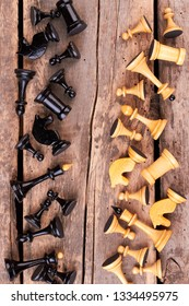 Abstract composition of chess figures. Black chess pieces against white chess pieces, top view. Rustic wooden background.