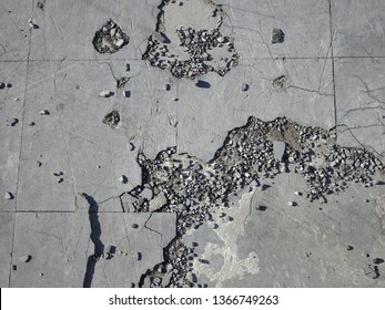 Abstract composition showing cracked concrete surface and loose gravel
