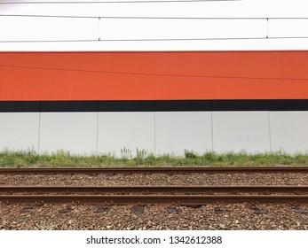 Abstract composition showing railway line,plus red and white striped factory wall background