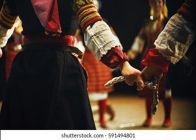Abstract composition showing women hands holding a bond, dressed in Serbian traditional clothe dancing in folklore.