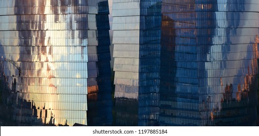 Abstract composition. Urban environment.  Three glass office skyscrapers in which the evening sky reflects.