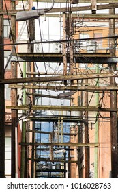 abstract composition of wooden telephone poles with power lines and transformers in a street back alley