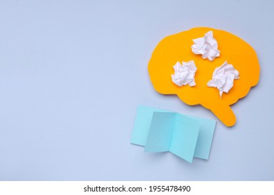 Abstract concept of analysing of informatio.Paper human brain,crumpled paper and blank paper for notes on the blue empty surface