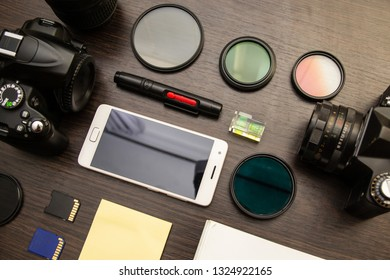 Abstract concept of modern photographer workplace: dark desk with photography gear, camera, lenses and acessories.