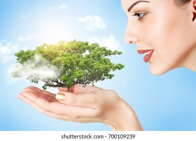 Abstract concept of woman holding a plant in her hands over blue sky background