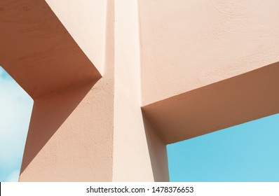 Abstract contemporary architecture fragment, pink painted concrete beams structure under blue sky