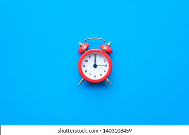 Abstract creative flat lay vintage blue table top view office background concept red clock on paper color in minimal style, Hot summer holiday time to break workplace at noon for lunch, Retro Hipster