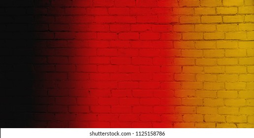 Abstract creative patriotic Background. Concept flag of Germany. Striped pattern of Vertical black, red and yellow stripes on Brick Wall Texture. Wallpaper or Web banner With free Space for text