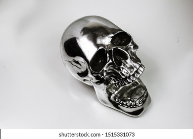Abstract Creepy Metallic Reflective Shiny Finished Chrome and Black Skeleton Bone Skull Cranium Head with its Mouth and Jaw Wide Open on an Empty Background