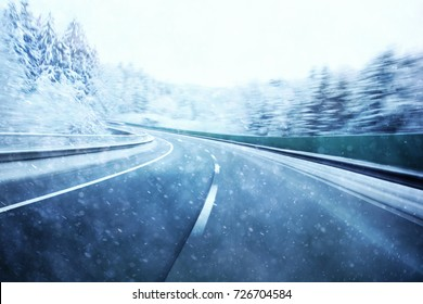 Abstract dangerous fast highway winter driving. Snowy conditions on the road. Motion blur visualizes the speed and dynamics.