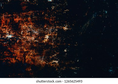 Abstract dark texture with grungy, dark black, brown, and red colors.