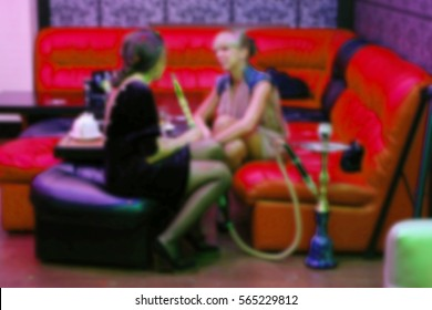 Abstract defocused background - beautiful, glamorous people relax and have fun. Entertains erotic show and smoking hookah. Blur Interior shisha club bar.
