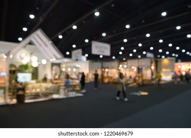 Abstract defocused blurred of public trade show expo event in modern exhibition hall background. MICE industrial business concept. International furniture fair expo home material or decor and garden.