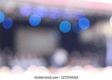 Abstract defocused bokeh lighting on stage during a concert with audience as a background with space in the middle.