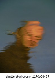 An abstract, deformed portrait of a man. Reflection in the water of an indistinct face with distorted features. A funny mirror. Natural reflection.