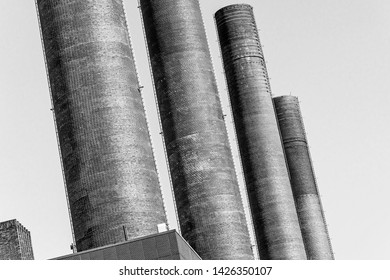 Abstract deliberately crooked image of the chimneys of the power plant of a large industrial plant, oblique