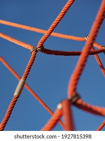 Abstract detail picture of climbing frame with red ropes and blue sky in playground