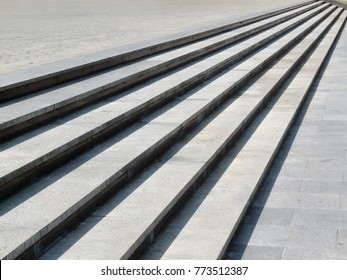 Abstract diagonal stairs, old worn granite staircase on a city square, wide stone stairway perspective often seen near monuments and landmarks. Pattern of long parallel geometric lines background.