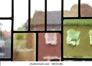 Abstract distortion of buildings through leaded glass.