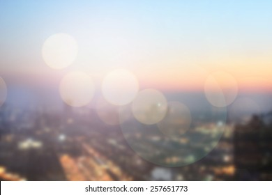 abstract double exposure of blurred sky night city downtown construction with circle round light background with lens flare effect concept.