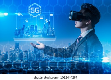 The abstract double exposure image of the business man wear a VR glasses hold the 5G hologram and cityscape is backdrop. The concept of 5G, communication, financial and internet of things.
