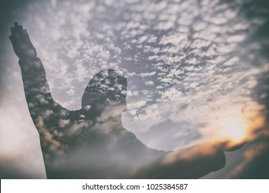 Abstract Double Exposure of Jesus Silhouette with Sunrise and Clouds.