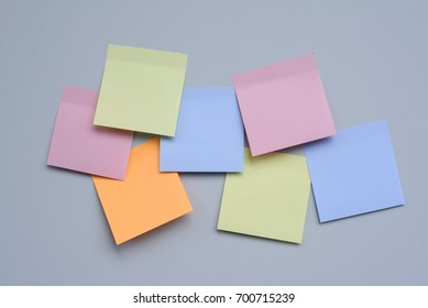 Abstract empty adhesive note paper on grey refrigerator door.  Colorful reminder paper note on metallic plate and copy space
