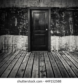 Abstract empty dark room interior background with gray wooden floor and black door in concrete wall