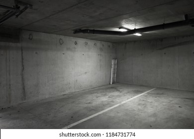 Abstract empty parking lot interior background with dark gray concrete walls and white ceiling lights