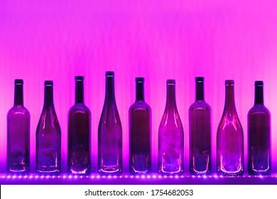 abstrakte leere Weinflaschen mit violetter Beleuchtung