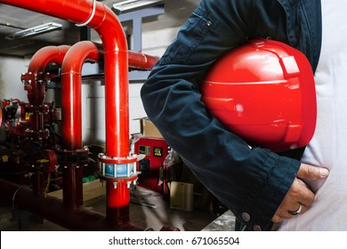 abstract engineer contractor holding red helmet with fire protection system background
