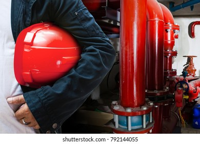 abstract engineer contractor holding red helmet with red pipe line for fire protection system background