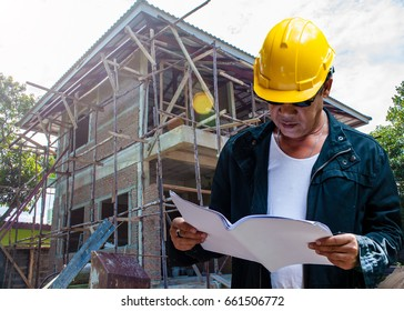abstract engineer contractor wear yellow helmet and holding house plan with under construction house background