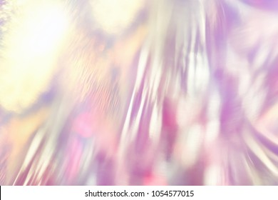Abstract fancy vibrant holographic foil background with shiny gleaming reflections and glittering bokeh light effect.