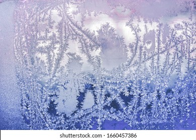 Abstract and fantastic icy patterns on frozen window glass. Hoarfrost effect texture. Blue winter background. Clear frosty ornament on surface. Christmas or winter backdrop. Rime or frost structure