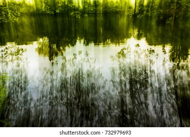 Abstract fine art photography with long exposure and intentional camera movement to obtain a soft dreamy landscape based on reflections and silhouettes.
