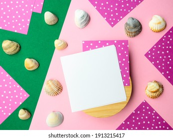 Abstract flatlay square note sheets on round wooden base,pink green diagonal paper background,corners of lilac paper,white polka dots on perimeter,scattered ivory seashells.Design pattern copy space.