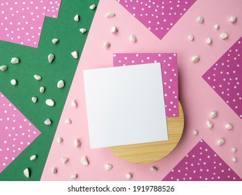 Abstract flatlay square note sheets on round wooden base,pink green diagonal paper background,corners of lilac paper with white polka dots around perimeter,scattered pebbles.Design pattern copy space